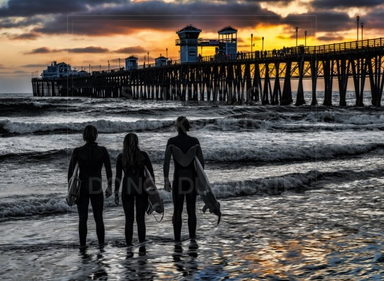 Surfers look on at sunset
