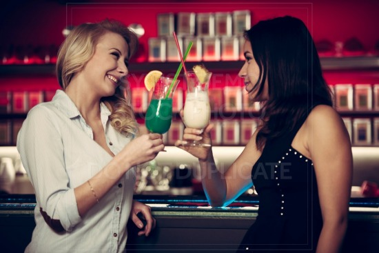 Two beautiful women drinking cocktail in a night club and having